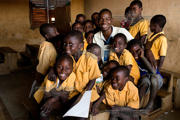 Francis Pii Kugbila with first grade students he teaches at Dagliga Primary school near Bolgatanga. When Kugbila became mentally unwell in 2009, his brothers took him to a traditional healer who forced his leg through a hole in a heavy length of tree trunk and pinned it in place, fashioning a crude restraint. Kugbila spent two years restrained in this manner, naked in a bare concrete room where he ate, slept and relieved himself. In late 2010 he came to the attention of mental health advocacy NGO, BasicNeeds, who arranged for him to receive appropriate treatment and negotiated for his release. Now fully recovered, Kugbila has been able to rebuild his family life and return to his profession as a teacher.