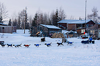 Martin Buser makes his way through the streets of Nikolai as he leaves the checkpoint during the 2010 Iditarod