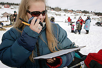 Volunteer checker Kaarin Andersson calls in dog traffice to the communications people at the White Mountain checkpoint on tuesday afternoon.