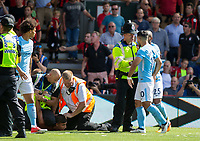 a Police officer holds back Sergio Aguero of Manchester City as he is unhappy how a supporters is treated during the Premier League match between Bournemouth and Manchester City at the Goldsands Stadium, Bournemouth, England on 26 August 2017. Photo by Andy Rowland.