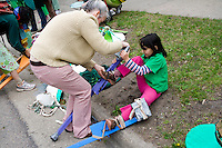 Mom helping daughter with adjustments for flowers on stilts parade unit. MayDay Parade and Festival. Minneapolis Minnesota USA
