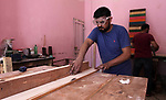 Palestinian man, Haitham Meqdad, 35 works on wood to make furniture at his workshop, in Gaza City, on June 20, 2019. Meqdad works with used wood boards and pieces to make artistic and creative furniture. Photo by Mahmoud Ajjour