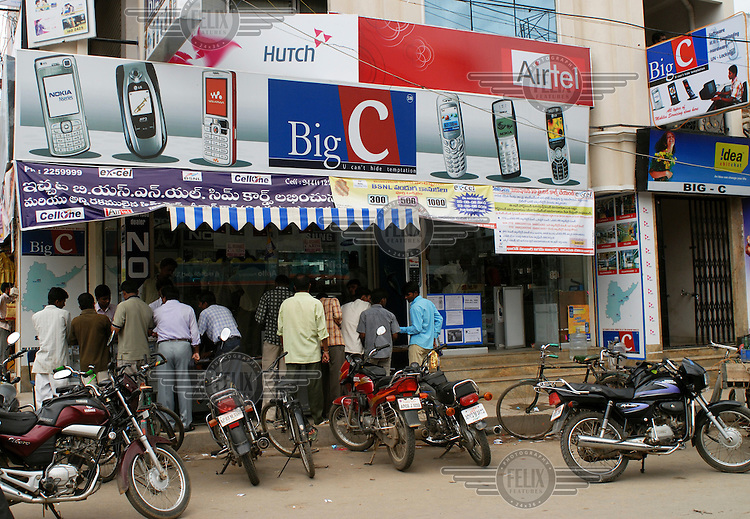 Customers crowd around the window display of the 'Big C' mobile phone store, which is located near a popular motorcycle parking spot. An advertising hoarding displaying various mobile phone brand names, including the Nokia brand, hangs above the shop....