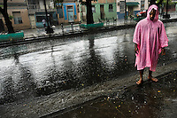 A Cuban man, wearing a pink raincoat, stands barefoot during a heavy rain on the street in the neighbourhood known for keeping the Afro-Cuban religious traditions in Santiago de Cuba, Cuba, 1 August 2009. The Palo religion (Las Reglas de Congo) belongs to the group of syncretic religions which developed in Cuba amongst the black slaves, originally brought from Congo during the colonial period. Palo, having its roots in spiritual concepts of the indigenous people in Africa, worships the spirits and natural powers but can often give them faces and names known from the Christian dogma. Although there have been strong religious restrictions during the decades of the Cuban Revolution, the majority of Cubans still consult their problems with practitioners of some Afro Cuban religion.