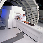 Technician preparing female patient for MRI procedure