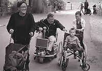 Family during a day out at a zoo. One of the children is playing, sitting in a wheelchair.