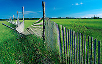 Weathered snow fence in a lush green field.