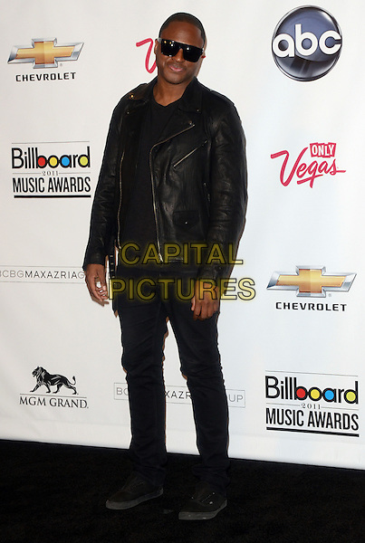 TAIO CRUZ.The 2011 Billboard Music Awards Pressroom held at the MGM Grand Garden Arena, Las Vegas, Nevada, USA..May 22nd, 2011.full length black leather jacket jeans denim top sunglasses shades .CAP/ADM/TW.©Tonya Wise/AdMedia/Capital Pictures.