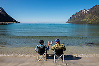 Two men in beach chairs with feet in sea at Ersfjord, Senja, Norway