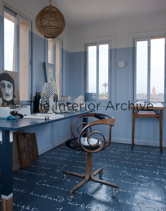 A retro chair cuts a sculptural shape on the blue-painted floor of the study which is covered in script