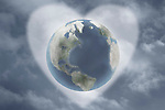 Earth in heart against cloudy sky, digital composite