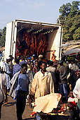 The Gambia. Rural market; selling meat from the back of a truck at the roadside; carcasses hanging in the truck.