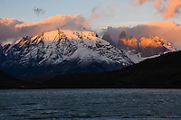 The famous towers of Torres Del Paine, Patagonian Chile, glow red  as the first rays of sunlight reach above the horizon.