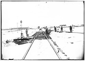 Section crew clearing snow from switches on main and station siding with railroad and town buildings in distance.<br /> St. Louis, Rocky Mountain &amp; Pacific Railway  Cimarron, NM  Taken by Troutman, Edward A. - ca 1909-1913