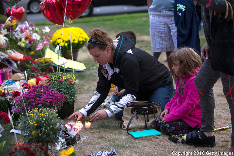 BURLINGTON, WA - SEPTEMBER 26: From left to right: Tawnee Larson and her daughter Caydence Larson, 7, from Burlington, Washington leave light candles at the memorial outside the Cascade Mall on September 26, 2016 in Burlington, Washington. They then joined hundreds of others for a candlelight vigil. Five people were shot and killed by a gunman several days ago. The suspect, Arcan Cetin, 20, a resident of Oak Harbor, Washington, made a court appearance today. (Photo by Karen Ducey/Getty Images)