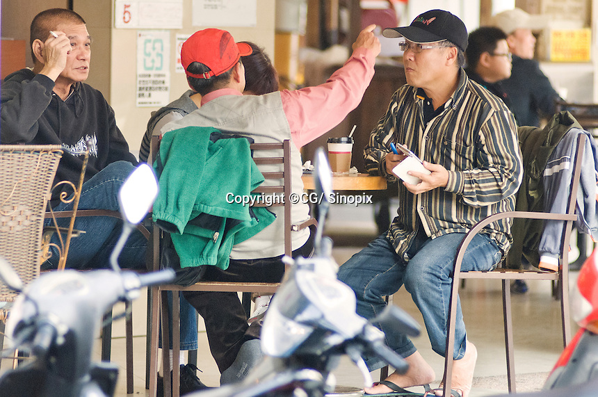 Gamblers/organisers sit outside a betting shop on Xi Jia Dong Lu in Taichung. The street is at the heart of syndicates that bet upon the cancer survival rates of terminally ill cancer patients in the city.<br /> <br /> Please credit photo by Sinopix