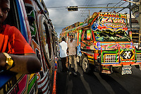 Tap-tap buses pass through the traffic chaos in the downtown of Port-au-Prince, Haiti, 26 July 2008. Tap-tap vehicles serve as public transportation in Haiti. They are private, operate over fixed routes, departing only when full. Tap-taps are decorated with bright and shiny colors and with a lot of fancy designed elements. There are scenes from the Bible, Christian slogans, TV stars or famous football players often painted on a tap-tap body. Tap-tap name comes from sound of taps on the metal bus body signifying a passenger's request to be dropped off.