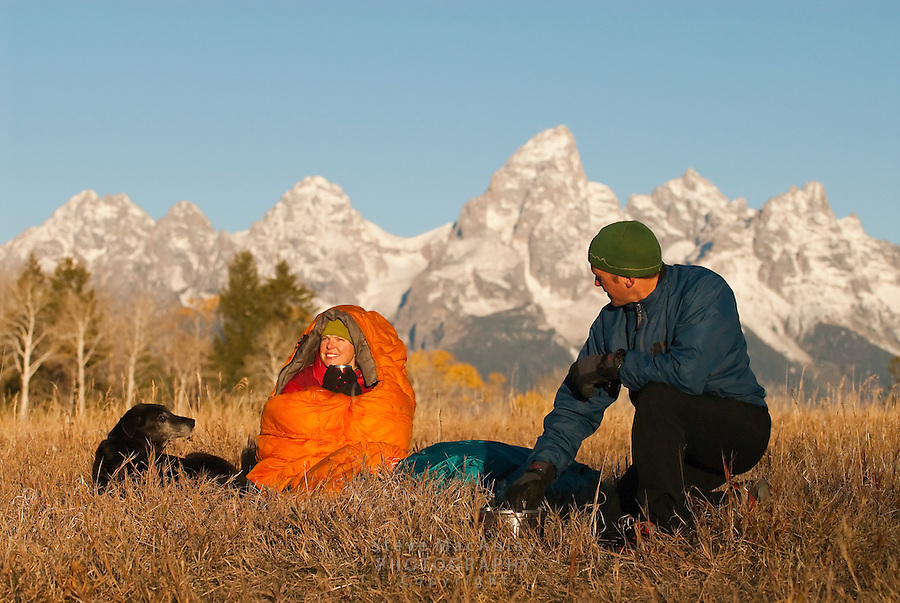 Man and woman enjoying cup of coffee on cold fall morning, Fall camping in Grand Teton National Park, Wyoming