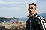 Fisherman Yoshiyuki Kumagai, 52, stands above the port in Ofunato. Photograph: Robert Gilhooly