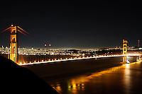 The Golden gate Bridge with glowing traffic flow and beaming off the waters of San Francisco Bay