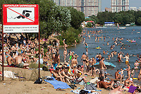 Moscow, Russia, 17/07/2010..A sign warning against swimming as Muscovites sunbathe and swim in lakes in northern Moscow during a prolonged heatwave that has seen temperatures of over 37C, a record for the city. Hundreds of Russians have drowned during the heatwave, most of them in bathing accidents after drinking alcohol.