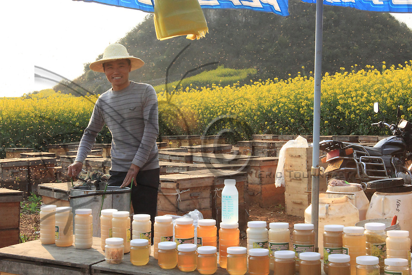 Luoping, Yunnan. A young beekeeper behind his stand uses a manual honey extractor for harvesting.