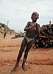 A boy plays with his friends along the dirt roads of Cape Coast, Ghana.