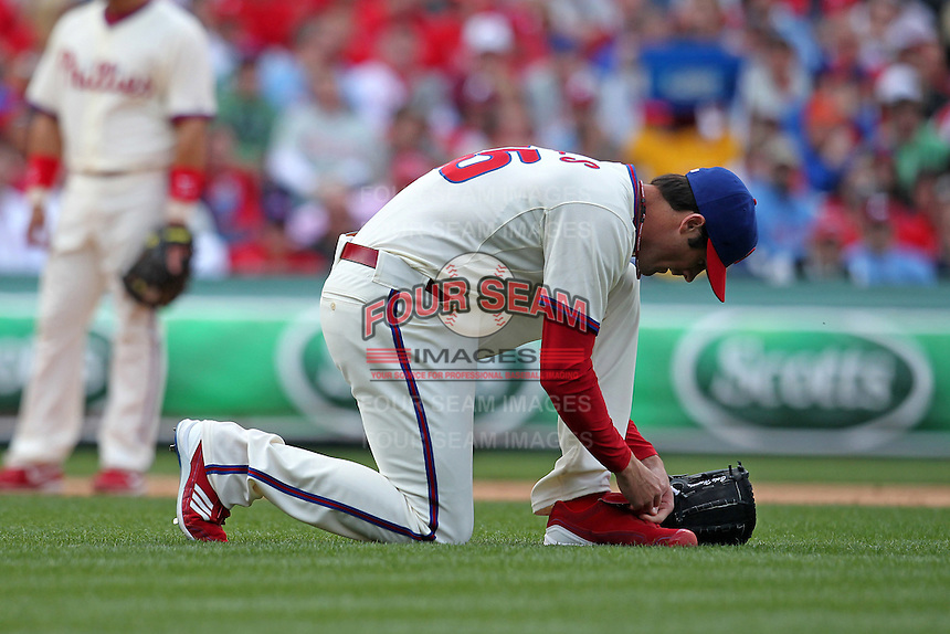 Philadelphia Phillies starting pitcher Cole Hamels #35 ties his cleats during their home opener against the Miami Marlins at Citizens Bank Park on April 9, 2012 in Philadelphia, Pennsylvania.  Miami defeated Philadelphia 6-2.  (Mike Janes/Four Seam Images)