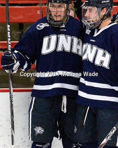 Kevin Goumas (UNH - 27), Austin Block (UNH - 3) - The Harvard University Crimson defeated the University of New Hampshire Wildcats 7-6 on Tuesday, November 22, 2011, at Bright Hockey Center in Cambridge, Massachusetts.