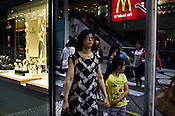 Pedestrians walk past a shop displaying the expensive rolex watches on their shop window in Central Macau, China.