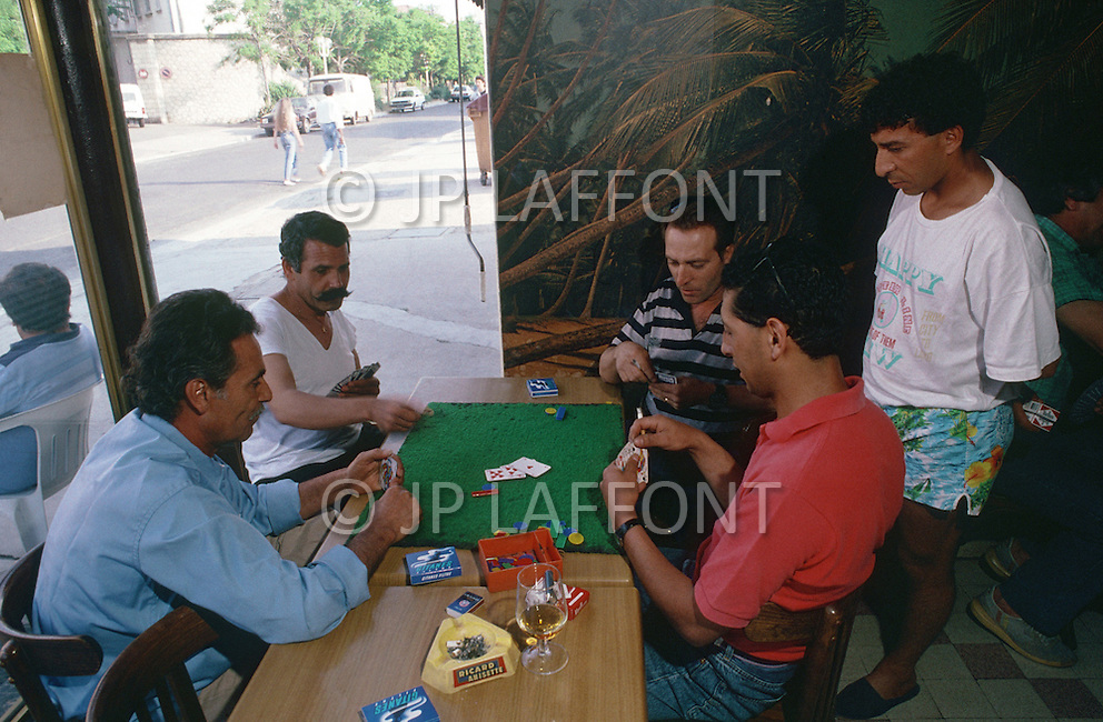 May 1989, Marseilles, France --- Muslim immigration in Marseille. Muslim men play games in a bar in Etang de Berre. --- Image by © JP Laffont