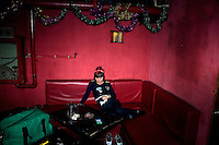 Xiao Na, bassist for the Chinese psychobilly band Angry Jerks, rests before the band's set begins at a concert at Castle Bar in Nanjing, China.