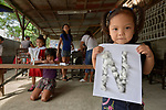 A girl shows off her class work--the letter N covered with glued-on cotton balls--in a preschool sponsored by the Kapatiran-Kaunlaran Foundation (KKFI) in Pulilan, a village in Bulacan, Philippines.<br /> <br /> KKFI is supported by United Methodist Women.