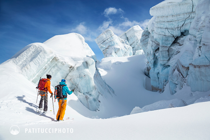 Two skiers looking at a glacier serac and crevasse while on a ski tour of the Schwarztor, Zermatt, Switzerland