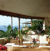The covered terrace with views over the sea is furnished with wicker seating and comfortable cushions