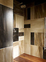 The shower room is sheathed in different sized horn tiles, and the floor is teak