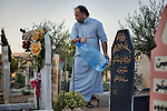 28/08/15. Shaqlawa, Iraq. -- Jaser, from Falluja, washes his father's grave in the new part of Shaqlawa's graveyard. His father died two months after arriving to Shaqlawa as a displaced person, early 2014.