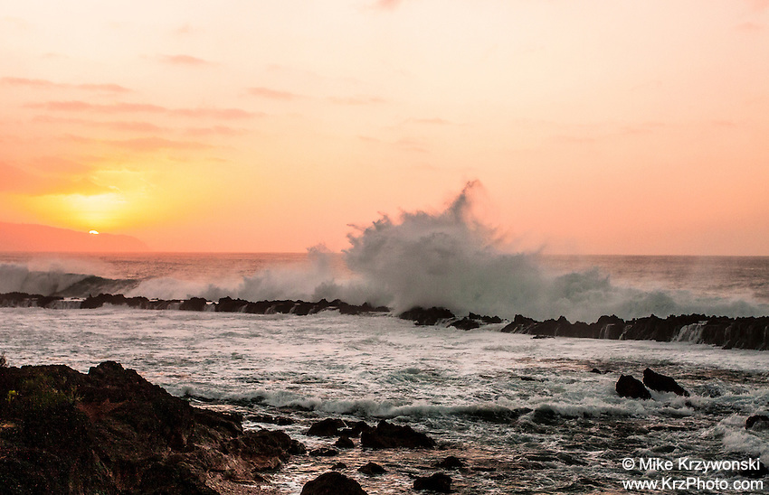 A large wave crashes on the rocks at Shark's Cove under an orange sunset on the North Shore of Oahu