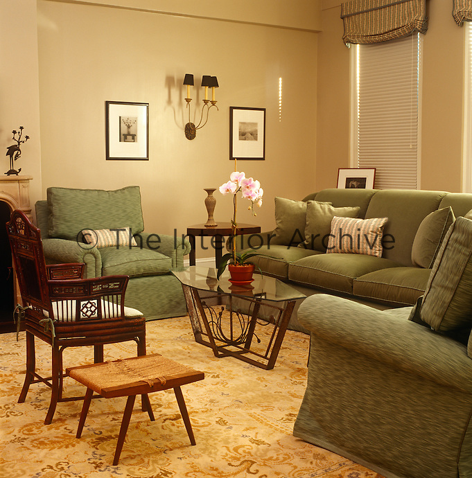 Shades of sage and olive in the colour of the sofa and armchairs of this New York living room give it a subtly retro feel