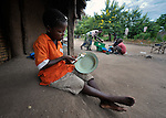 """Gota Dzongololo, 11, eats sorghum porridge in the morning after getting dressed in his school uniform. He lives in Chidyamanga, a village in southern Malawi that has been hard hit by drought in recent years, leading to chronic food insecurity, especially during the """"hunger season,"""" when farmers are waiting for the harvest."""