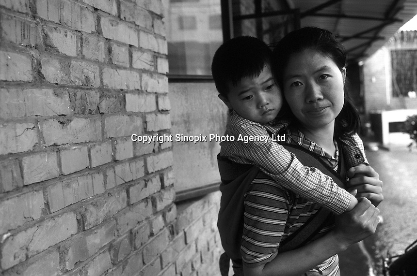 Tan Qin (29) has her son Guo Yang (5) strapped to her back. Guo Yang was rescued from a rich man of fifty called Wang Yu Sheng who had three daughters of his own and adopted a mentally handicapped boy. He wanted a son to and heir. Guop Yang is scared to leave his mothers sides after the drama which included abuse. The boy calls all strangers bastards...PHOTO BY SINOPIX