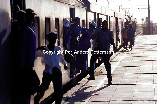ditrtra00054 .Transport, trains. Commuters leaving a train from central Cape Town at  Nonqubela train station on August 15, 2001 in Site B Khayelitsha, a township about 35 kilometers outside Cape Town, South Africa. Khayelitsha is one of the poorest and fastest growing townships in South Africa. People usually come from the rural areas in Eastern Cape province to find work as maids and laborers. Most people don't find work and the unemployment rate is very high, together with lot of violence and a growing HIV-Aids epidemic itÕs a harsh area to live in..©Per-Anders Pettersson/iAfrika Photos.