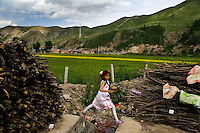 A girl jumps over a garbage pit in Xiahe, Gansu, China.  Xiahe, home of the Labrang Monastery, is an important site for Tibetan Buddhists.  The population of the town is divided between ethnic Tibetans, Muslims, and Han Chinese.