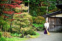Monk raking up leaves, Nikko, Japan