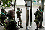 14 MAY 2010 - BANGKOK, THAILAND: Thai troops observe anti-government street protesters on Rama IV Road in Bangkok Friday. Thai troops and anti government protesters clashed on Rama IV Road Friday afternoon in a series of running battles. Troops fired into the air and at protesters after protesters attacked the troops with rocket and small homemade explosives. Unlike similar confrontations in Bangkok, these protesters were not Red Shirts. Most of the protesters were residents of nearby Khlong Toei slum area, Bangkok's largest slum area. The running battle went on for at least two hours.   PHOTO BY JACK KURTZ
