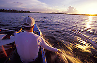 Surfer in local outrigger canoe dragging his hand in water at sunset, Siargao Island, Philippines