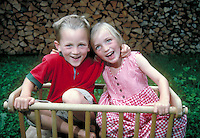 Smiling boy and girl in wagon. Leoni and Claudius. Germany.