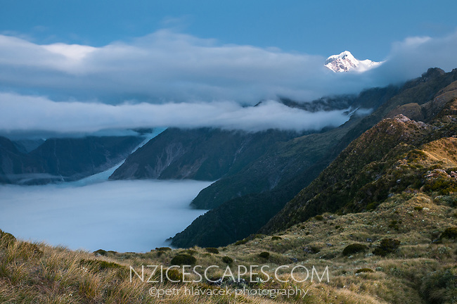 View of Fox Glacier through cloud formation from Mt. Fox after sunset, Westland Tai Poutini National Park, UNESCO World Heritage Area, West Coast, New Zealand, NZ