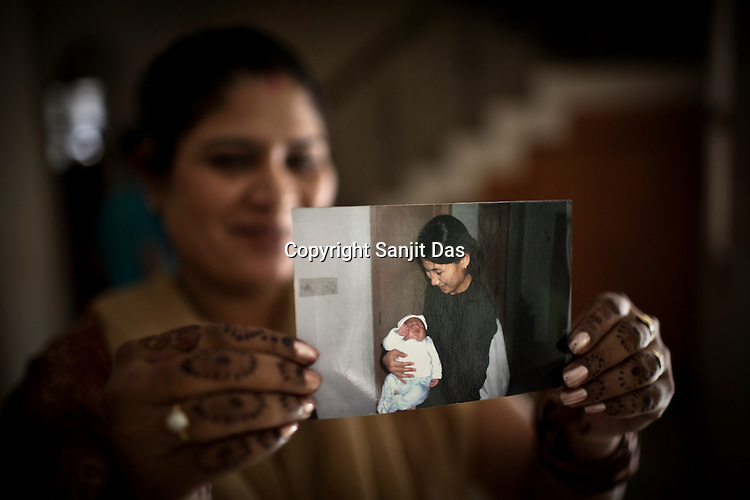 Surrogate mother for first western couple, Rabina Mondal (31) shows the file photograph of Karen Kim with her son Brady who the first baby to a western couple delivered on February 2nd 2007 at the Akanksha Infertility Centre & IVF Centre in Anand, Gujarat, India. Rabina  now mentors surrogate mothers and houses women throughout their pregnancy.