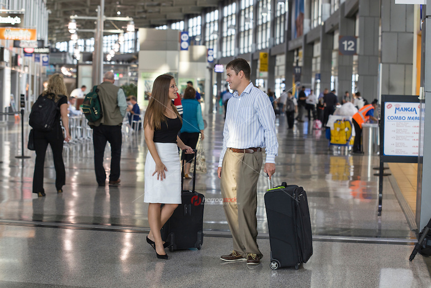 Attractive young business couple smiling while killing time at the Austin airport terminal.